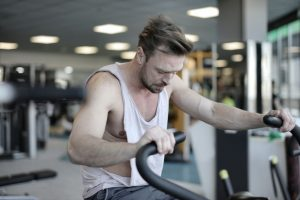 tired sportsman using exercise-bike during training in gym