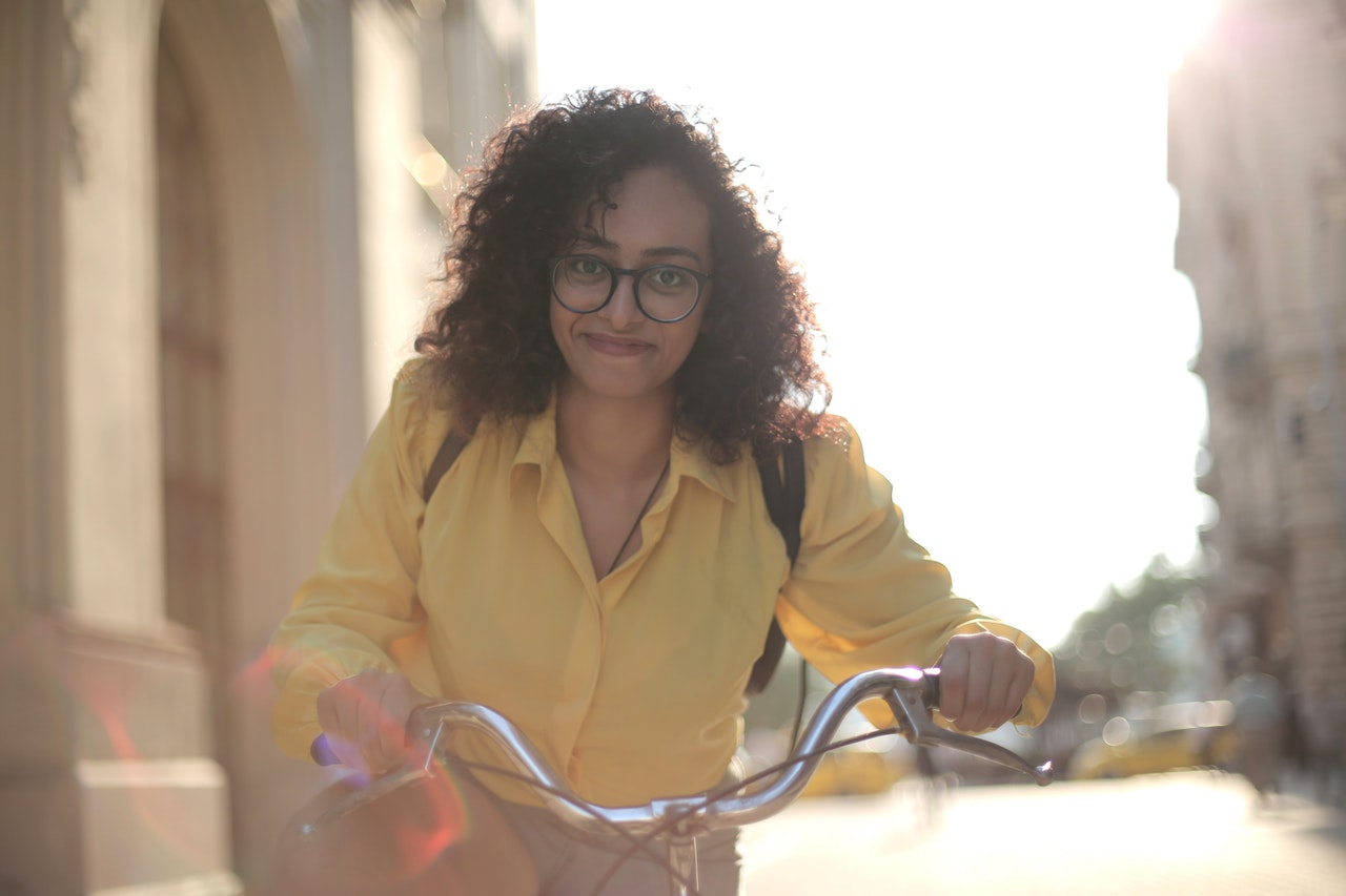 a girl with curly hair holding bike