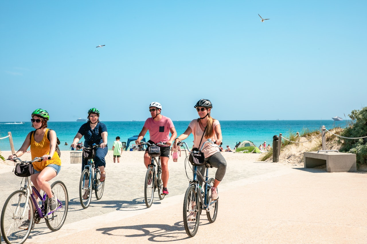 group of people riding bike by the beach